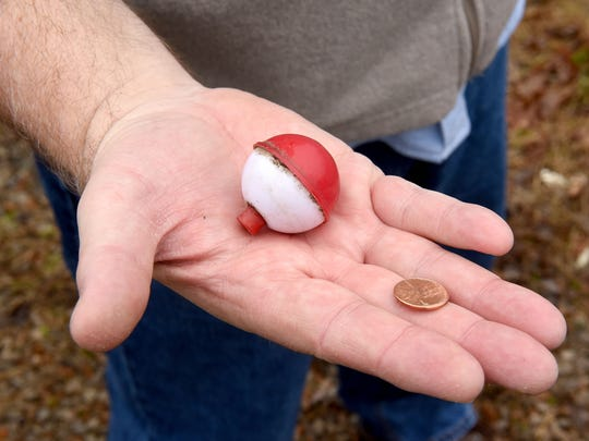 "Kenn Kiser, founder of Clean Up Litter In Coshocton, shows his ""profits"" from an afternoon of picking up trash along County Road 1A in Coshocton - a penny and a fishing bobber."