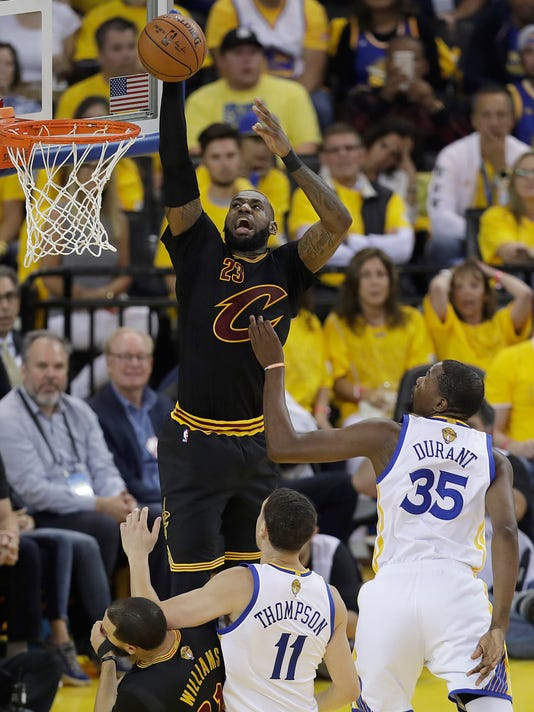 Cleveland Cavaliers forward LeBron James (23) dunks over Golden State Warriors guard Klay Thompson (11) and forward Kevin Durant (35) during the first half of Game 5 of basketball's NBA Finals in Oakland, Calif., Monday, June 12, 2017. (AP Photo/Marcio Jose Sanchez)