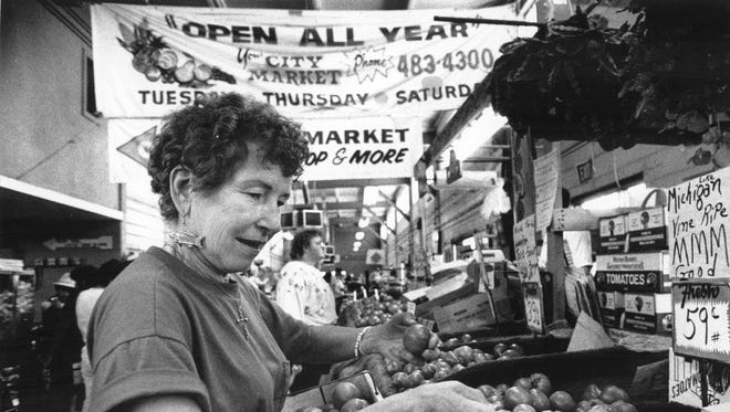 Barney Yeager puts fresh tomatoes in her booth at the Lansing City Market in June, 1990.