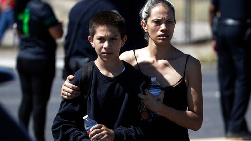 Christina Marquez, right, picks up her son Angelo Marquez at the scene of a school bus crash Thursday, May 4, 2017, in Las Vegas. Angelo Marquez was in a the school bus during the crash.