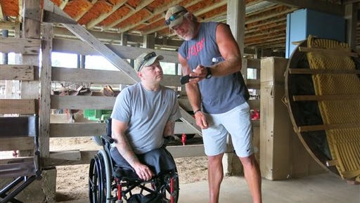 Retired NFL quarterback Brett Favre, right, and U.S. Army veteran Rusty Dunagan trade hunting stories and photos inside a barn at the Lauderdale County, farm of actress Sela Ward on Monday.
