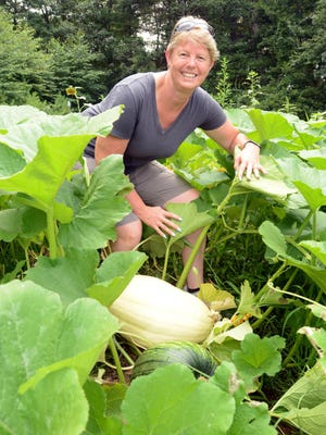 Firefighters Elizabeth Bragg shows a Dill's Atlantic Giant Pumpkin still growing at Central Village Fire Company No. 1 in Central Village Wednesday in a patch of about 200 pumpkins at the firehouse.