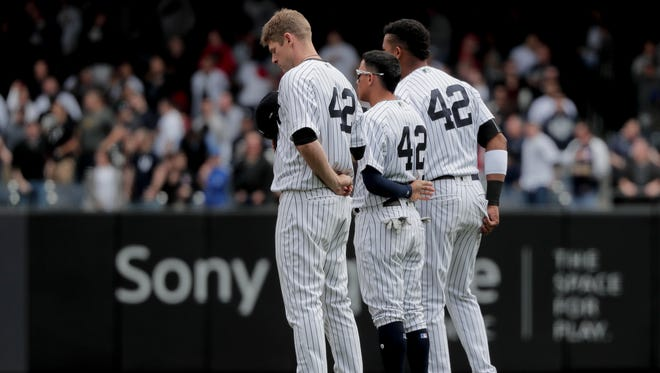 Yankees players all wear the No. 42 as they stand at second base for the national anthem before the start of a baseball game against the St. Louis Cardinals, Saturday, April 15, 2017, in New York. Saturday's game was designated Jackie Robinson day in which all the players from both teams wore the number 42.