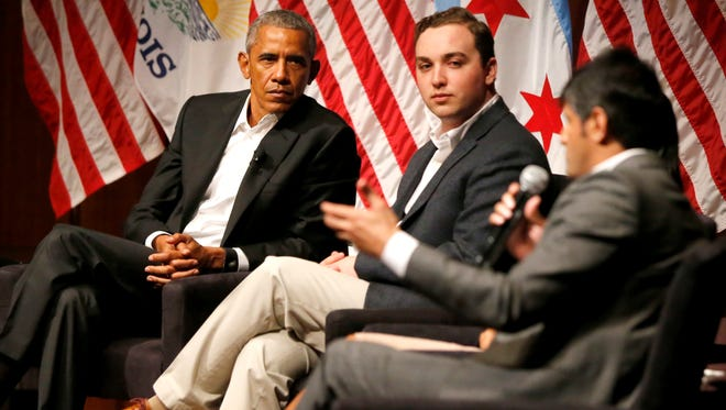 Former President Barack Obama and Max Freedman, center, listen to Harish Patel speaks during a conversation on civic engagement and community organizing, Monday, April 24, 2017, at the University of Chicago in Chicago. It's the former president's first public event of his post-presidential life in the place where he started his political career.