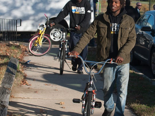 Camden PowerCorps members Shannon Murphy, front,  and Jaleel Carson walk their bikes home after a bike donation by the Camden County freeholders. About 20 bikes where given to Camden residents to help them get to work.