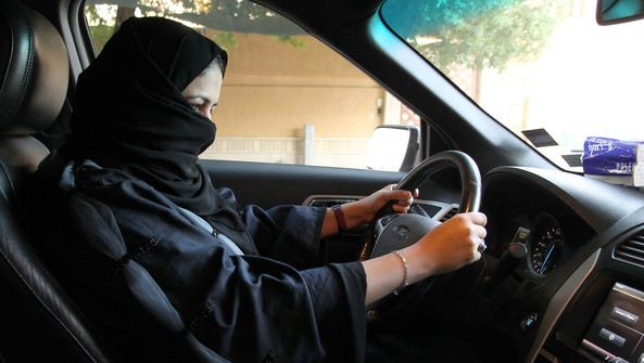 A woman sits behind the wheel of a car in Riyadh, Saudi
