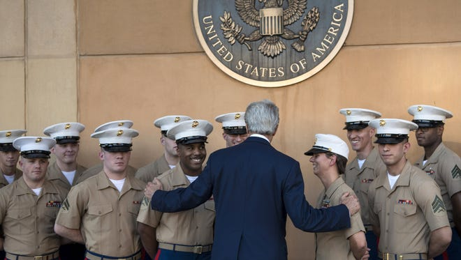 Secretary of State John Kerry greets U.S. marines as he arrives at the U.S. embassy in the International Zone on June 23 in Baghdad.
