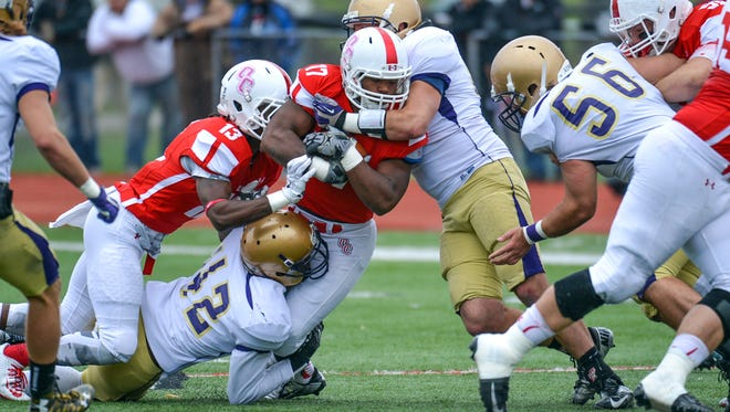 Albion defenders work to bring down Olivet running back Andre Houston during their 2015 matchup.