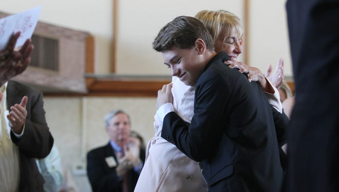 Sarah Owen of the Southwest Florida Community Foundation is congratulated by her son Samuel after being named The News-Press 2016 Person of the Year.