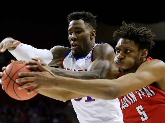 Kansas forward Jamari Traylor, left, fights for a rebound