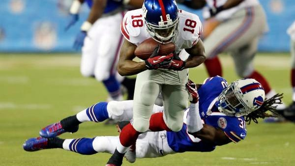 Giants wide receiver Marcus Harris (18) tries to break away from Buffalo Bills defensive back Mario Butler in the second quarter of the Pro Football Hall of Fame game Sunday night in Canton, Ohio.