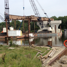 Construction crews lay the beams for the bridge over the Grand River.