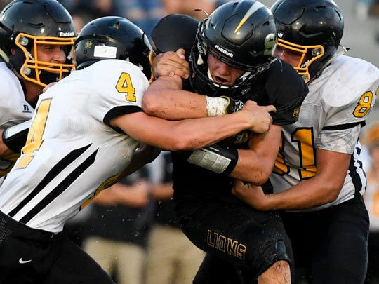 Scotts Hill's Ty Martin is grabbed and tackled by an