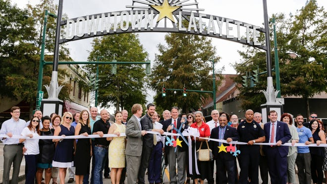 """Mayor-President Joel Robideaux, surrounded by community leaders, prepares to cut the ribbon for the new """"Downtown Lafayette"""" sign on Jefferson Street Sept. 15, 2016."""