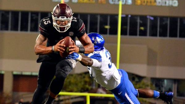 Oct 24, 2015; Starkville, MS, USA; Mississippi State Bulldogs quarterback Dak Prescott (15) scores a touchdown after breaking a tackle by Kentucky Wildcats defensive end Denzil Ware (35) during the first quarter of the game at Davis Wade Stadium.
