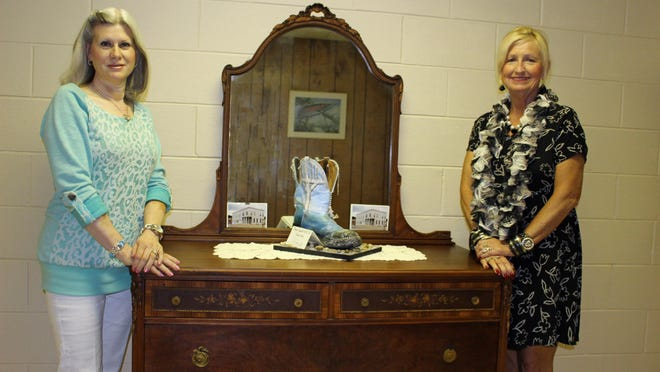 Danna Huddleston-Hunt, right, of Flippin presents Cotter Mayor Peggy Hammack with an antique dresser which was in the original Miser Hotel in Cotter at the turn of the 20th century The Miser Hotel later became the Waverly Hotel.