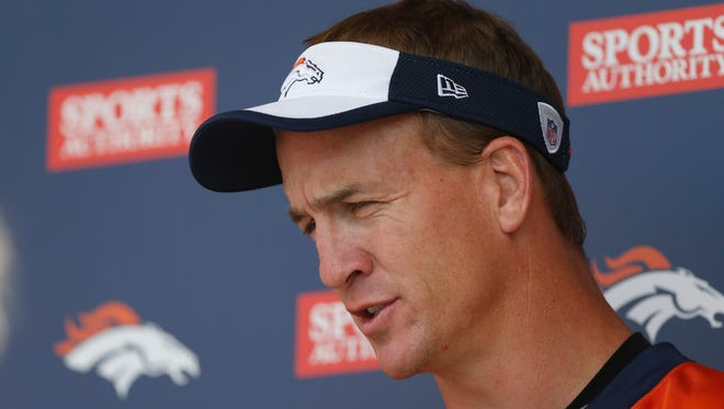 Denver Broncos quarterback Peyton Manning talks with reporters after an NFL football organized team activity Wednesday, May 27, 2015, in Englewood, Colo.