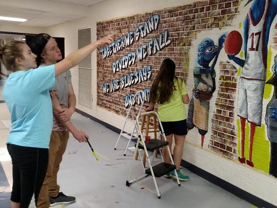 Art students from Merrill High School are shown collaborating on an original 6-foot by 25-foot graffiti mural.