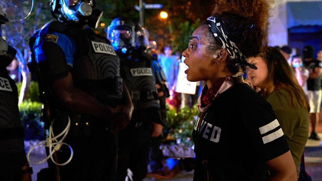 Lily Nicole talks with officers with the Wilmington Police Department during a confrontation between protesters and police in downtown Wilmington on Sunday.
