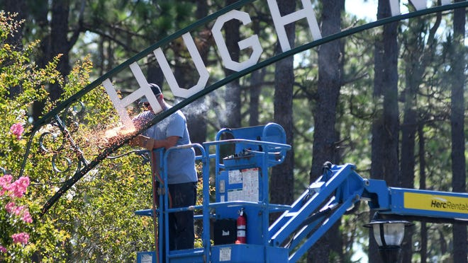 Crews with New Hanover County take down the sign at the entrance of Hugh MacRae Park in Wilmington, N.C., Tuesday, July 14, 2020.