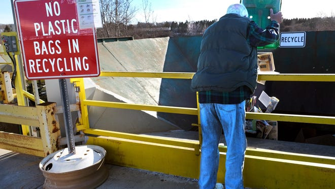 A Portsmouth resident empties a recycle bin into a single-stream hopper at the city's recycling center.