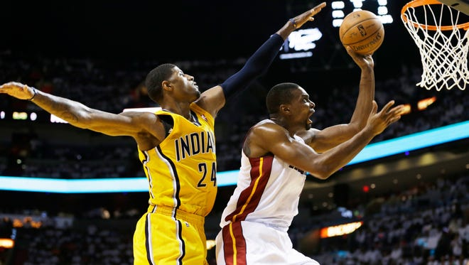 Miami's Chris Bosh, right, drives to the basket as Indiana's Paul George defends in the second half of Game 3 of the Eastern Conference finals on Saturday.