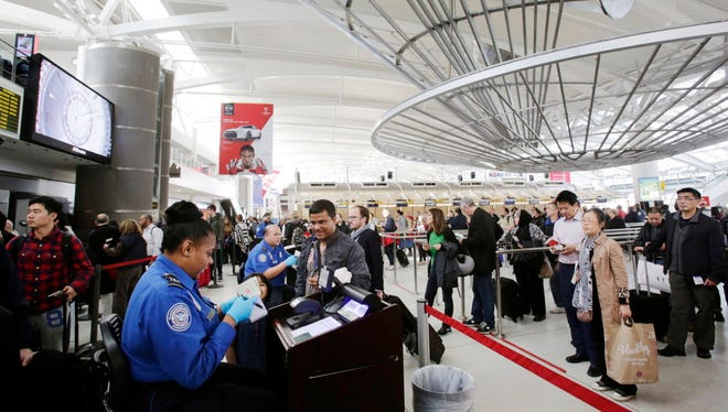 A Transportation Security Administration officer checks a passenger's ticket, boarding pass and passport as part of security screening at John F. Kennedy International Airport in New York on Oct.  30, 2014.