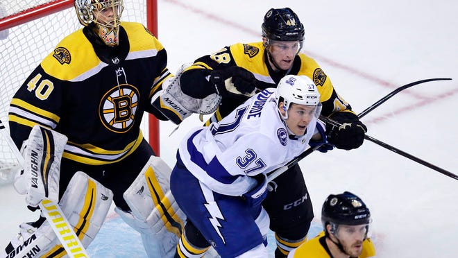 Boston Bruins defenseman Matt Grzelcyk (48) tries to clear Tampa Bay Lightning center Yanni Gourde (37) away from the goal during the third period of an NHL hockey game in Boston, Thursday, March 29, 2018. At left is Bruins goaltender Tuukka Rask.