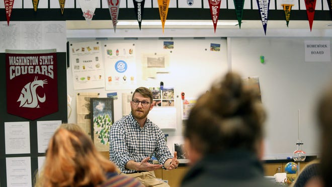 Bainbridge High School AP Environmental Science teacher Jason Uitvlugt answers questions in his class.