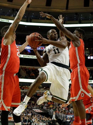 Michigan State's Lourawls Nairn Jr. (11) passes as he drives between Ohio State's Amir Williams, left, and Jae'Sean Tate, right, in the first half  Friday, March 13, 2015.