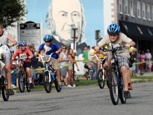 Dylan McIntosh, right, races in the nine- and 10-year-old age group boys bike race Friday, July 25, 2014, on Wheeling Street in Lancaster. McIntosh took first place in his age group.