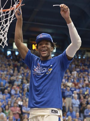 Kansas Jayhawks guard Devonte' Graham (4) cuts a piece of the net after the win over the Texas Tech Red Raiders at Allen Fieldhouse. Kansas won 67-58, winning their twelfth consecutive Big 12 titles.