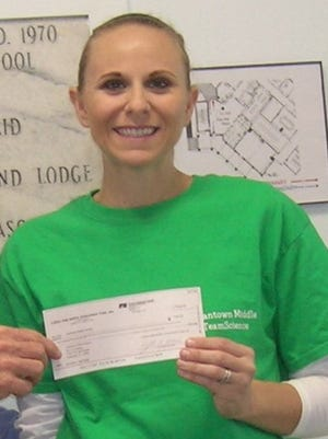 Indiantown Middle School teacher Lisa Knapp received a $250 check from Florida Farm Bureau Federation to use agriculture in teaching her students.
