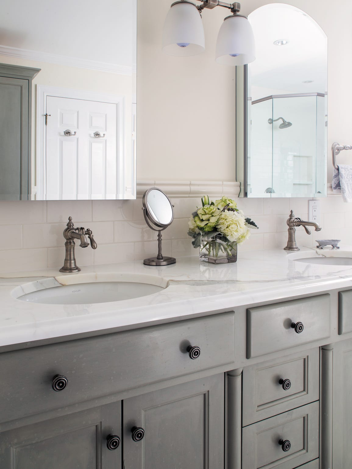 Gray and white carry through in bathrooms for a traditional-chic