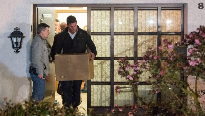 Police carry computer, a box and bags out of the residence of the parents of Andreas Lubitz, co-pilot on Germanwings flight 4U9525. The photo was taken on March 26 in Montabaur, Germany.