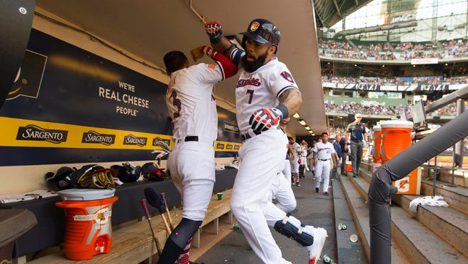 Eric Thames (right) celebrates in the Brewers dugout after hitting the first of his two solo home runs on the afternoon in the fifth inning against the Orioles on Tuesday at Miller Park.