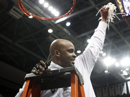 Missouri State Bears Head Coach Cuonzo Martin shows off the remains of the net after he cut the last piece after the Bears defeated the Wichita State Shockers clinching the Missouri Valley Conference title at JQH Arena on Saturday, Feb. 26, 2011.