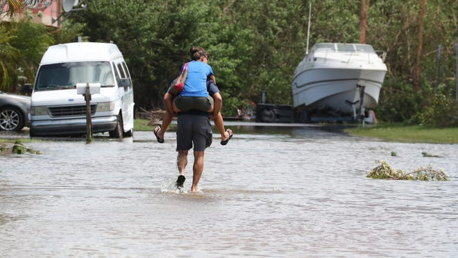 """Vince carries Arlene Camarca to their home. """"Im tired of having wet feet"""" Arlene said.  Flooding in a few pockets and a lot of tree damage through out could be seen in Iona-McGregor area. This area was hit hard two weeks ago with heavy rain and now they will have to dig out from Hurricane Irma."""
