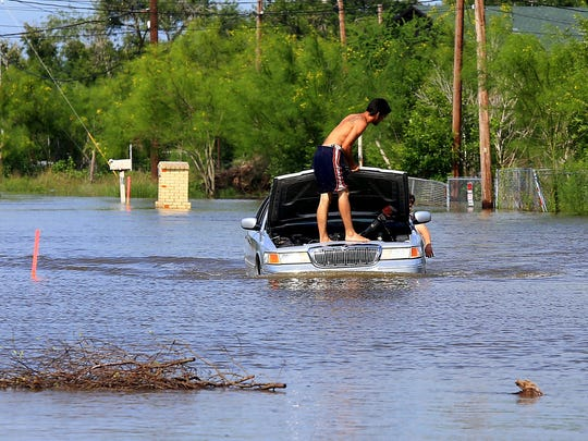 JJ Volger stands on top of a car as he keeps an eye on the engine after recent rains and the Nueces River filling its capacity Tuesday May 19, 2015 on Ware Rd. in Corpus Christi.