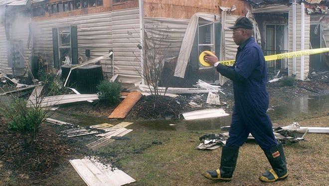 Jackson Fire Department Investigator Greg Travis cordons off the fire scene in 2001.