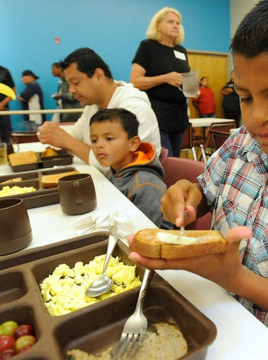 Marco Magana III butters his toast while having breakfast at The Banquet with his brother Mario, 4, and dad Marco Jr. in Sioux Falls, S.D., Thursday, July 9, 2015.