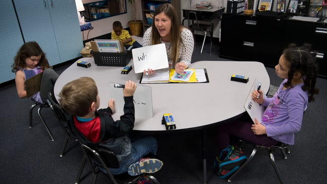 Kayla Stallings, a Title 1 instructionalist at Delaware Elementary School, challenges her students, from left, Jazlyn Gibson, Jack Godshall and Aryannah Gordon, with spelling words Wednesday morning.