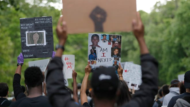 People hold signs as they march in Boston, Tuesday, June 2, 2020, to protest against police brutality following the death of George Floyd, who died after being restrained by Minneapolis police officers on Memorial Day.