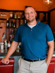 Tannin General Manager Chris Roelofs stands in front of the bar of the Okemos location.