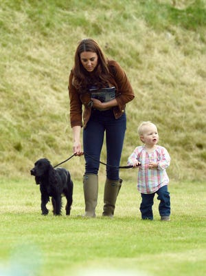 Duchess Kate walks Lupo with Savannah Phillips, a young royal cousin, at a charity polo match in Tetbury, England in June 2012.