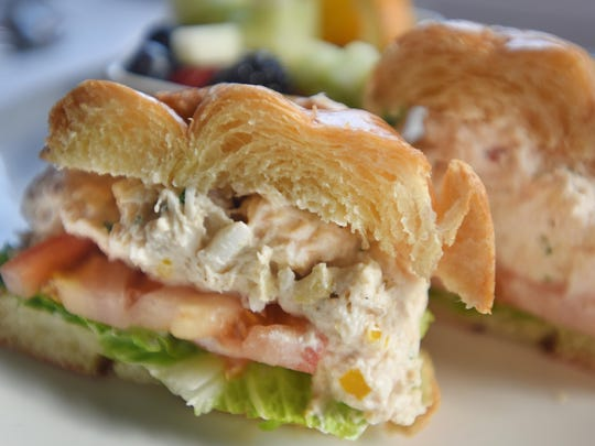 The crab and shrimp salad sandwich served on croissant with romaine, tomato, peppers, chives and lemon aioli.