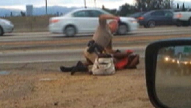 Image made from video provided by a motorist shows a California Highway Patrol officer punching a woman on the shoulder of a Los Angeles freeway.