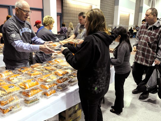 Volunteer DeWayne Mareck gives out sandwiches during