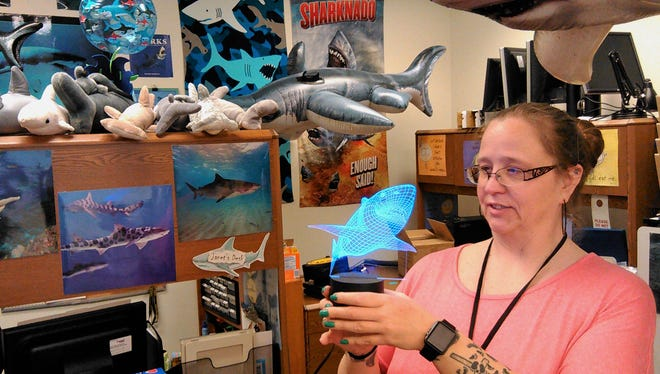 Sharks, sharks and more sharks line Janet Lubben's office at the North Liberty Community Library.  Her passion for this predatory fish is revealed in inflatables, posters, stuffed sharks and the LED art she holds.