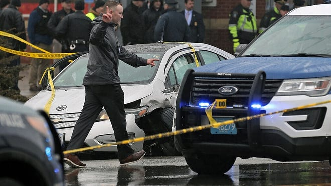 In this Feb. 7 file photo, police investigate the scene of a shooting at the intersection of Route 9 and Hammond Street in Brookline that started near Brigham and Women's Hospital in Boston.